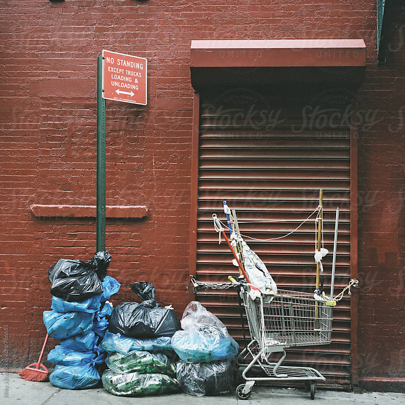 Bags of trash & shopping cart in front of a red wall by Riley J.B. for Stocksy United