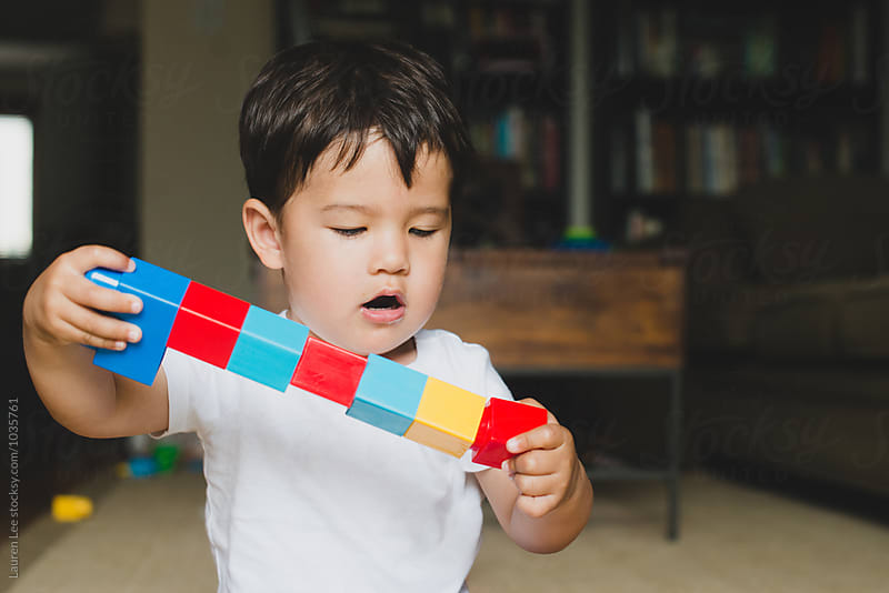 Child playing with building blocks by Lauren Naefe for Stocksy United