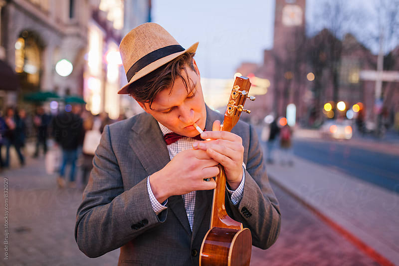 Young man in a classic suit holding a ukelele lighting his cigarette by Ivo de Bruijn for Stocksy United