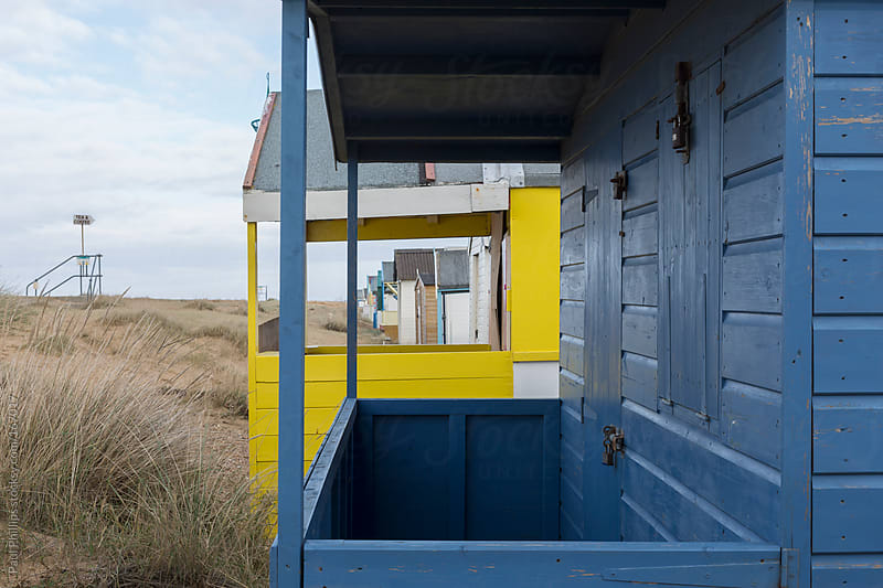 View through several beach huts on the coastline by Paul Phillips for Stocksy United
