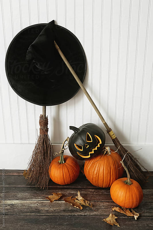Witch hat, broom and pumpkins near wall on floor by Sandra Cunningham for Stocksy United