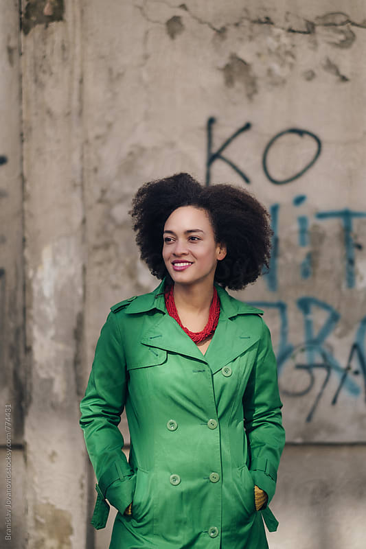 Portrait of a Smiling Young Woman in Green Trench Coat by Branislav Jovanović for Stocksy United