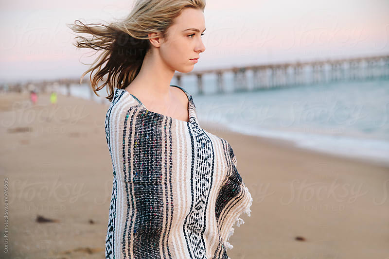 Young blonde girl on the beach with blanket over her by Curtis Kim for Stocksy United