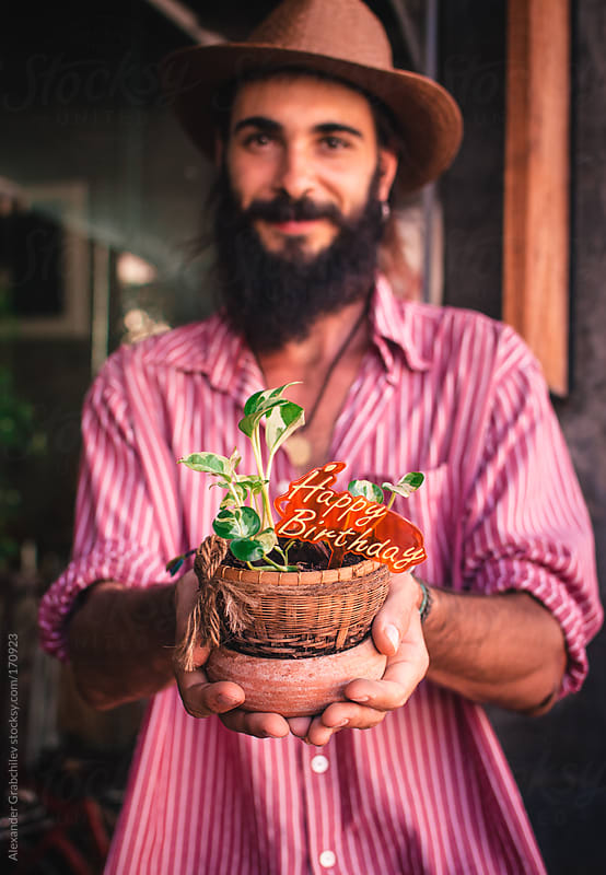 bearded young man holds flower pot by Alexander Grabchilev for Stocksy United