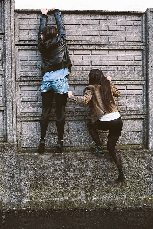 Two girls climbing the wall by michela ravasio for Stocksy United