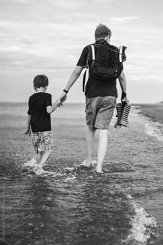 Dad and son hold hands as they walk in the sea by Rebecca Spencer for Stocksy United