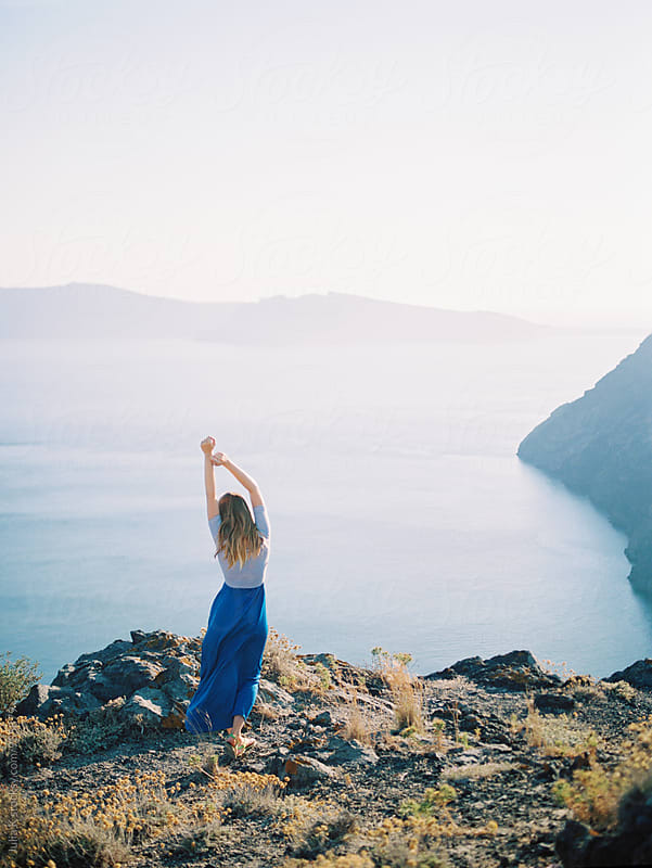 Woman enjoying landscape of Santorini, Greece by Julia Kaptelova for Stocksy United