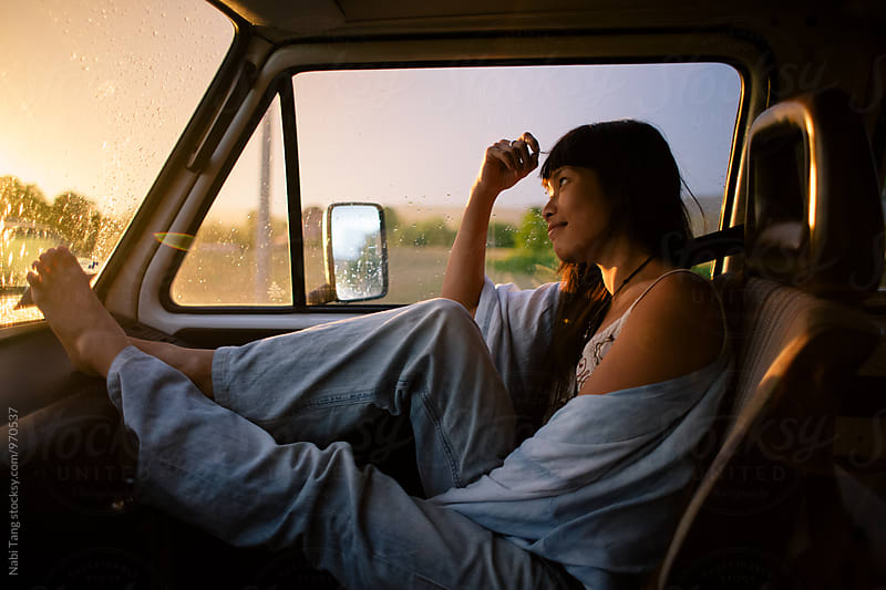 Asian young woman enjoying sunset in the front seat of the camper van by Nabi Tang for Stocksy United