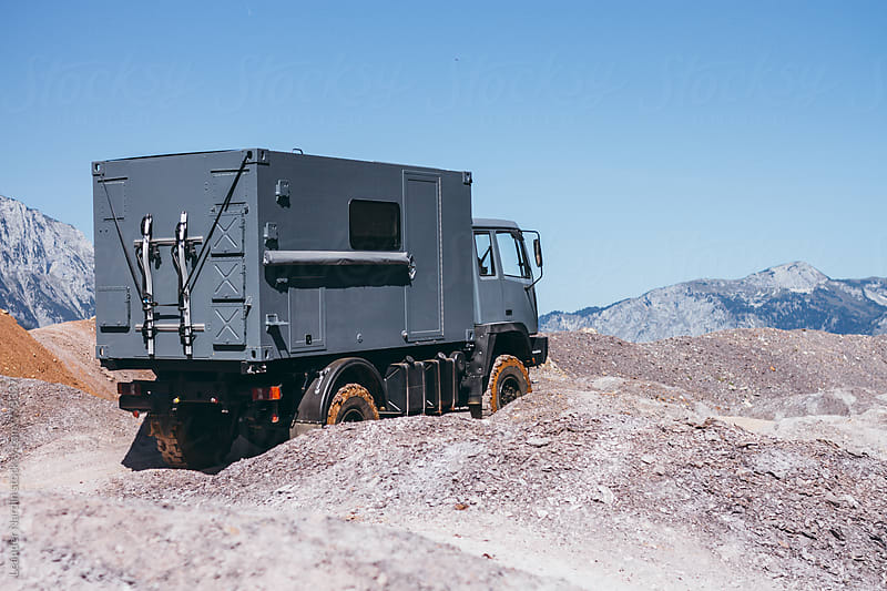 grey offroad truck in rugged landscape by Leander Nardin for Stocksy United