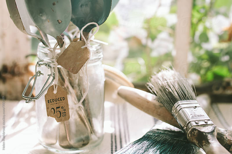 Paintbrushes and spoons with paint on them. by Helen Rushbrook for Stocksy United