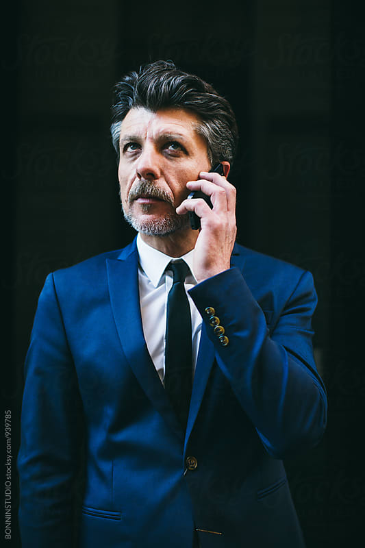 Mature businessman talking on phone. by BONNINSTUDIO for Stocksy United