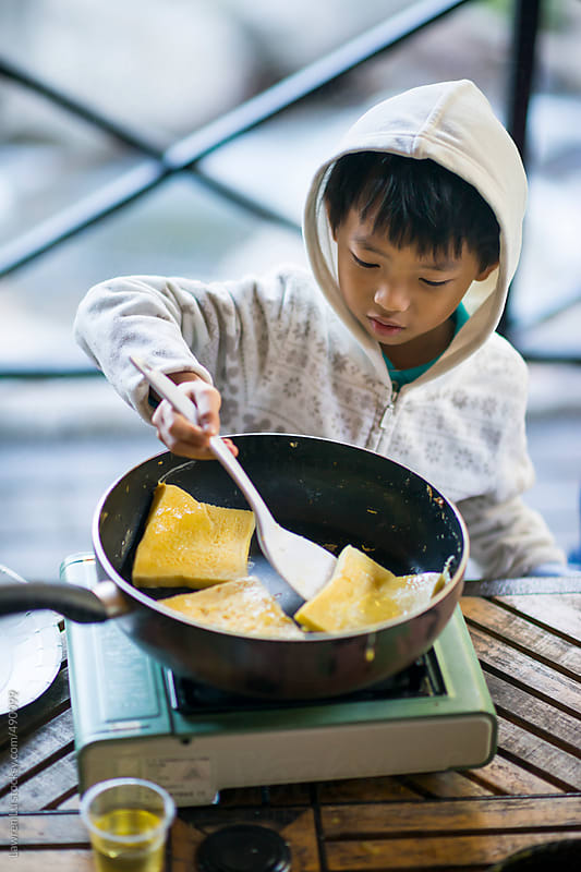 Kid frying French toast with spatula by Lawren Lu for Stocksy United