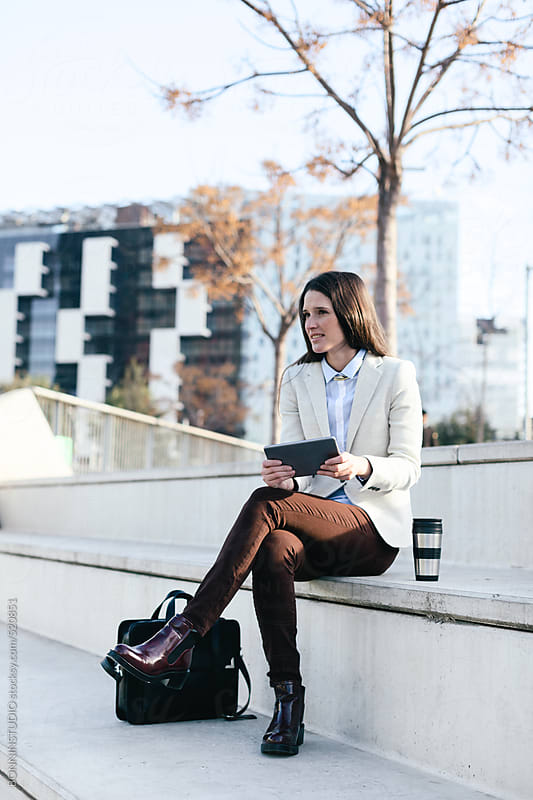 Young woman sitting in outdoors and using a digital tablet for work. by BONNINSTUDIO for Stocksy United