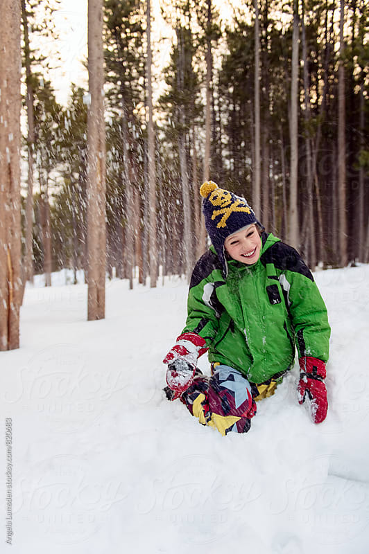 Boy playing in deep snow ducks as a snow ball lands nearby by Angela Lumsden for Stocksy United