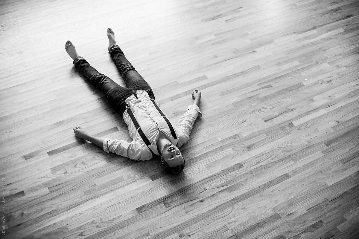 Man lying on the hardwood floor by J