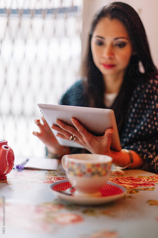Brunette Asiatic Using a Digital Tablet while drinking a Cup of Tea by HEX. for Stocksy United