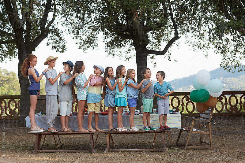 Ten children playing on a bench at an outdoors party by Miquel Llonch for Stocksy United
