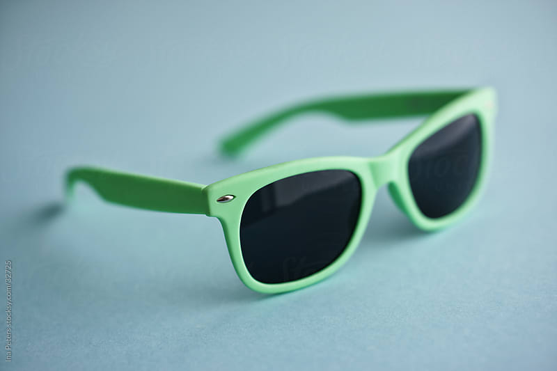 Objects: Pastel green sunglasses on blue background by Ina Peters for Stocksy United
