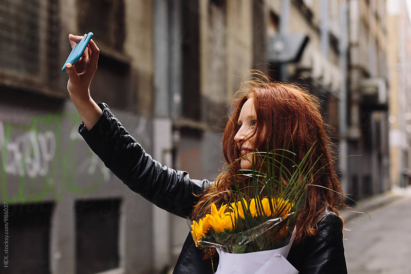 Young Beautiful Woman Taking a Self Portrait Holding Flowers after a Date by HEX. for Stocksy United