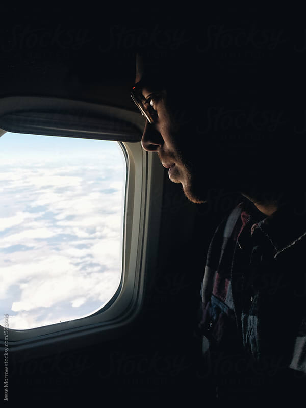 Young man looks out window in airplane by Jesse Morrow for Stocksy United