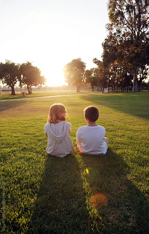 young girl and boy sitting together at park by Dina Giangregorio for Stocksy United