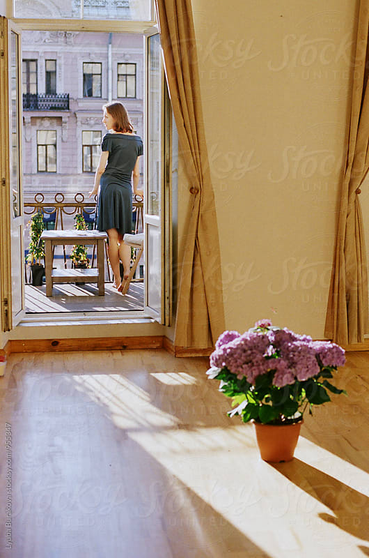 Young woman standing on a balcony by Liubov Burakova for Stocksy United