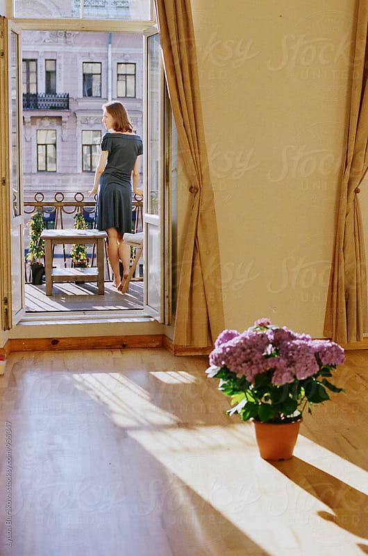 Young woman standing on a balcony by Lyuba Burakova for Stocksy United