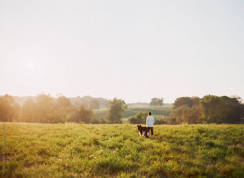 With his dog by Marta Locklear for Stocksy United