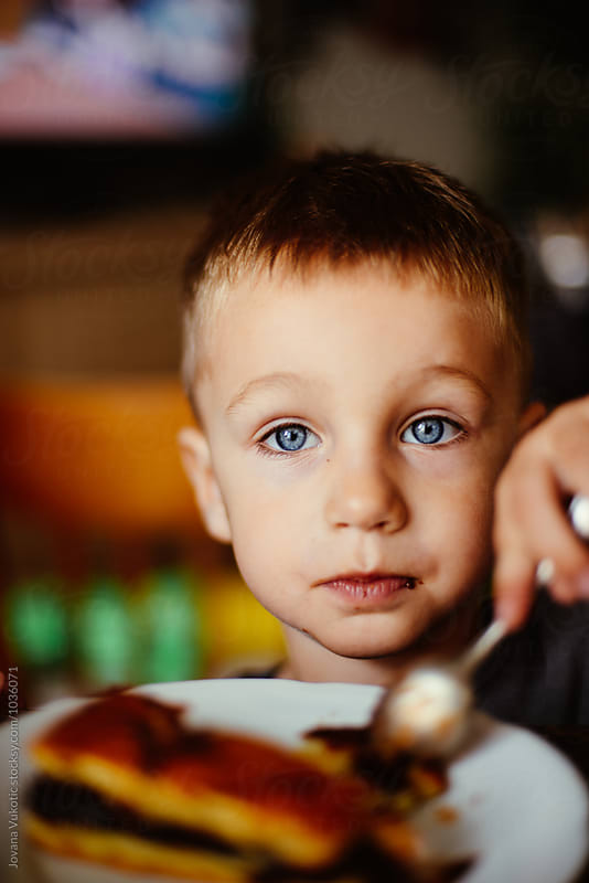 boy eats a cake by Jovana Vukotic for Stocksy United