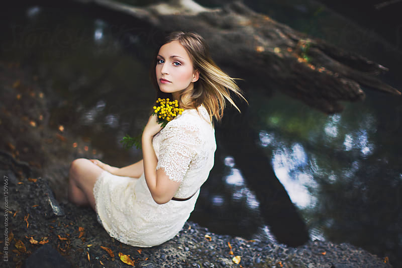 Girl sitting by a creek by Ellie Baygulov for Stocksy United