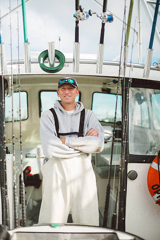 Proud boat captain standing in doorway of cabin. by Kate Daigneault for Stocksy United