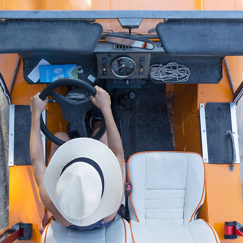Overhead view of a woman driving an orange car by ACALU Studio for Stocksy United
