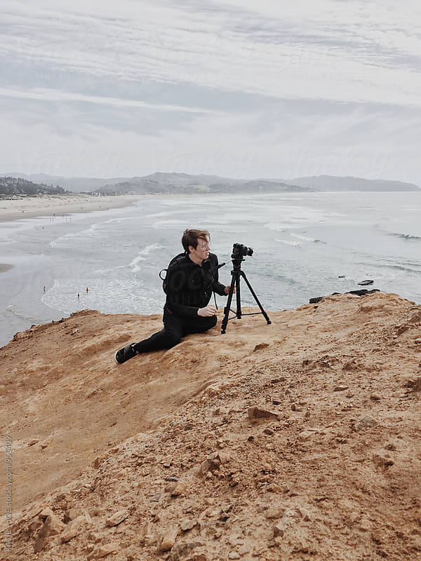 man sitting on the edge of a cliff with a tripod by the ocean by KATIE + JOE for Stocksy United