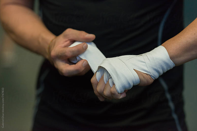 fighter tying tape around his hand preparing to box by Gabriel Diaz for Stocksy United
