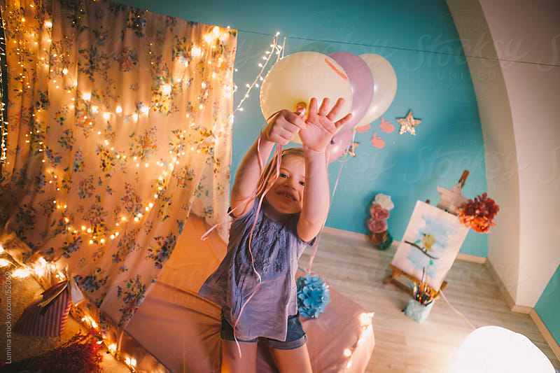 Girl Playing With Balloons in Her Room by Lumina for Stocksy United