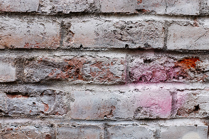 Paint covering graffiti on old brick wall by Paul Edmondson for Stocksy United