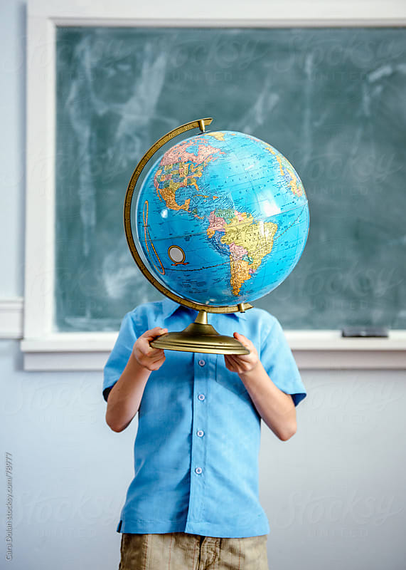 Child standing in classroom holds a globe up in front of his face by Cara Dolan for Stocksy United