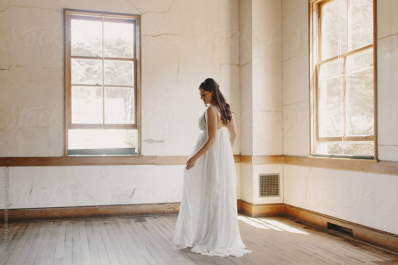 Bride in front of Winows by Sidney Morgan for Stocksy United