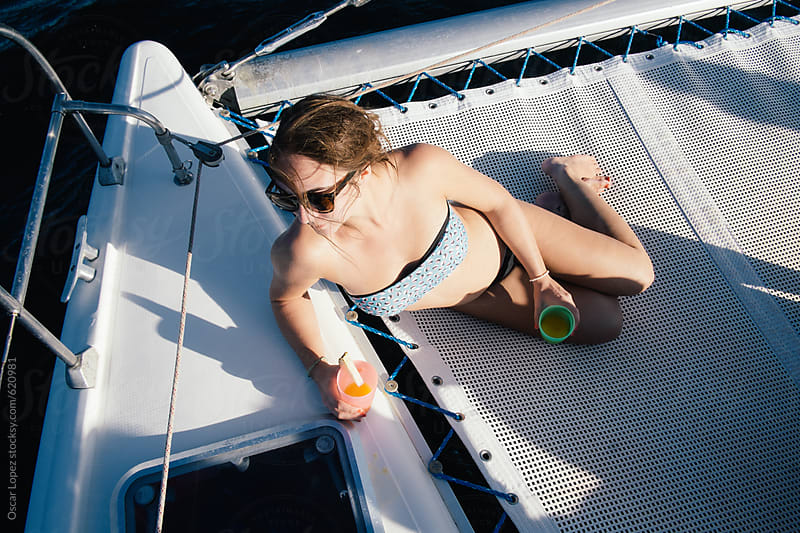 Woman lounging on a yacht by Oscar Lopez for Stocksy United