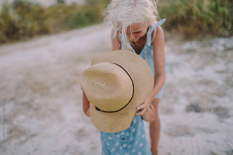 Little girl try on the hat her younger sister  by Evgenij Yulkin for Stocksy United