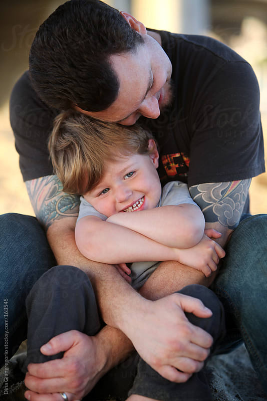 Dad with tattoos hugging toddler  by Dina Giangregorio for Stocksy United