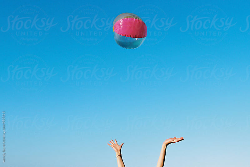 rainbow beach ball thrown in air by wendy laurel for Stocksy United