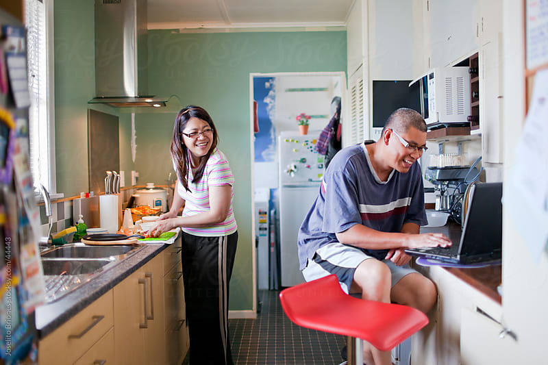 Husband Using Laptop and Wife Cooking in Kitchen Together by Joselito Briones for Stocksy United