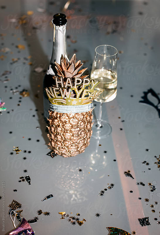 A bottle of champagne with a glass and a golden pineapple with happy new year headband by Beatrix Boros for Stocksy United