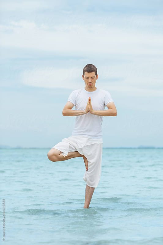 Young man practicing yoga at the beach. by Mosuno for Stocksy United