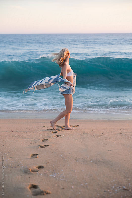 Beautiful blonde girl dancing on the beach by Curtis Kim for Stocksy United