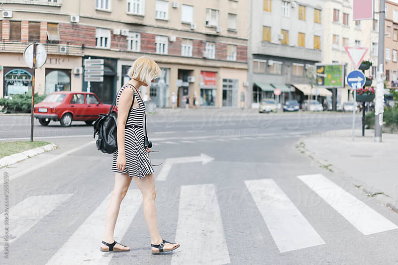 Blonde woman crossing the street by Marija Kovac for Stocksy United