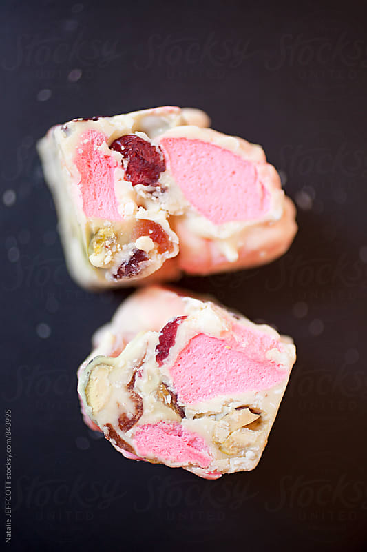 Close up macro of sweet treat - white chocolate rocky road with pink marshmallow on a black plate by Natalie JEFFCOTT for Stocksy United