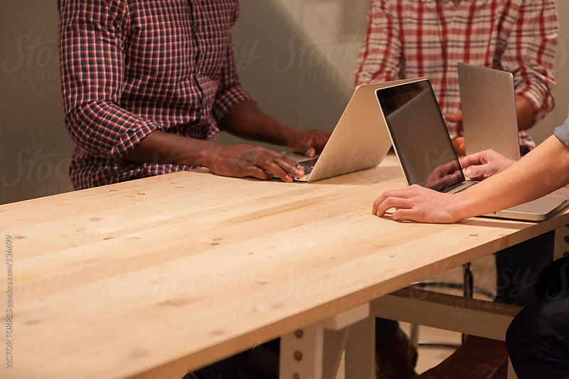 Three people Working on a Wooden Table by VICTOR TORRES for Stocksy United