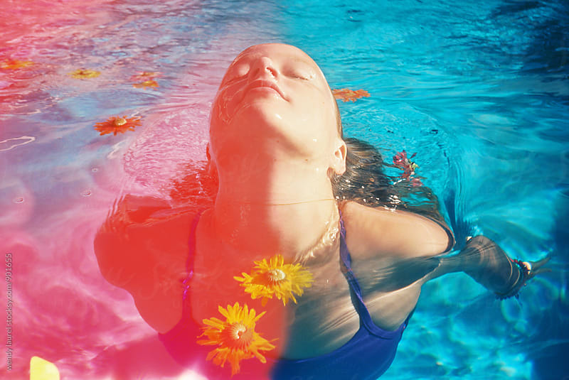 light leaked photo of girl swimming with colorful flowers in pool by wendy laurel for Stocksy United